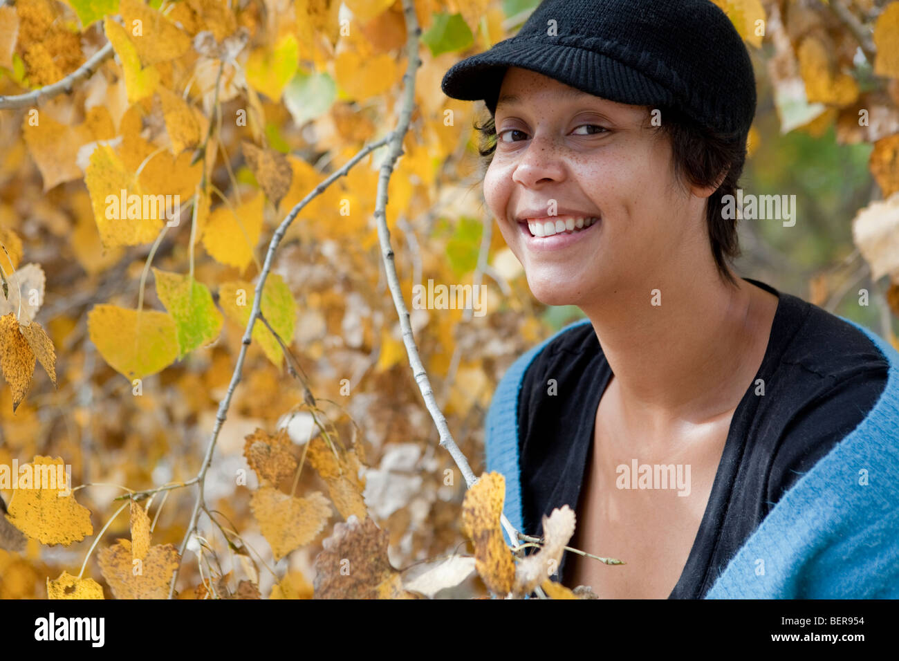 Portrait of a smiling, freckled, light skinned black woman - Stock Image