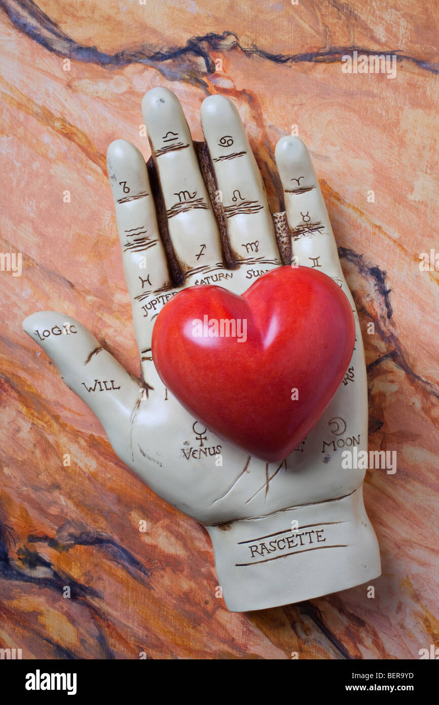Palm reader hand holding red stone heart - Stock Image