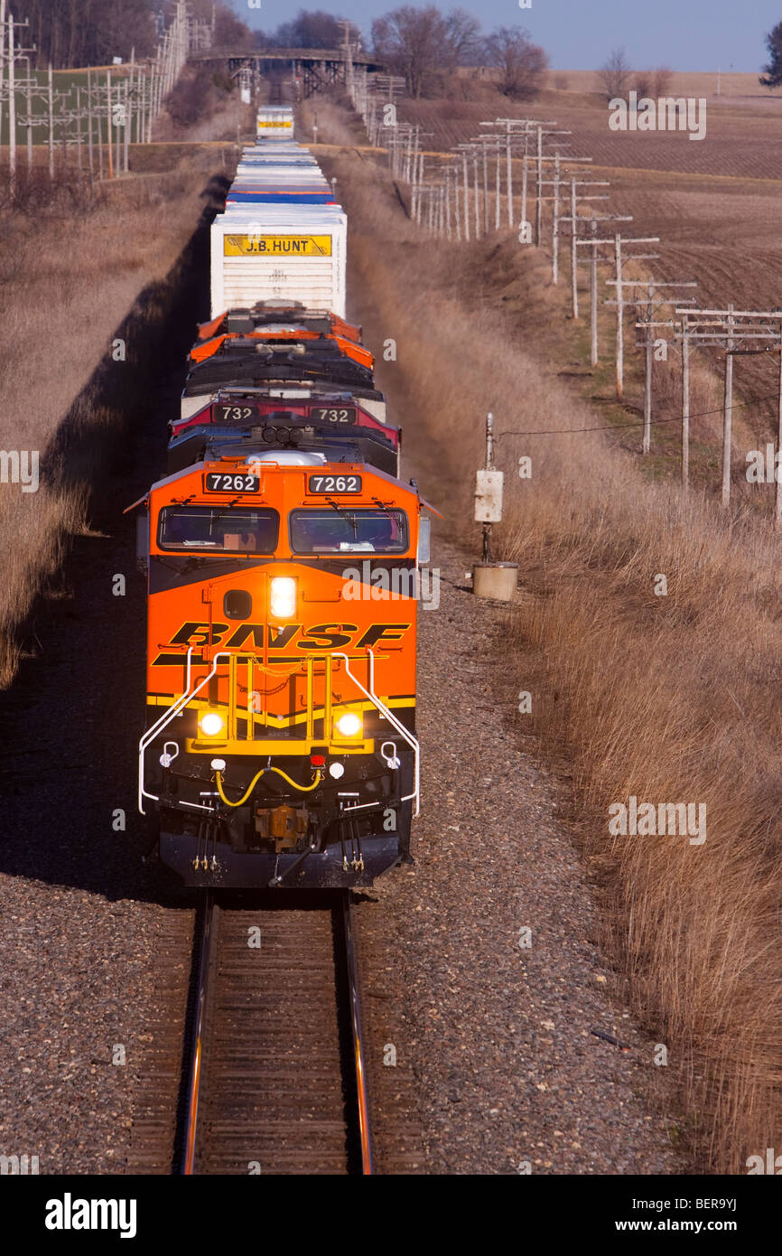 With a brand new locomotive leading the way, a BNSF intermodal train heads west across the plains of the Midwest. - Stock Image