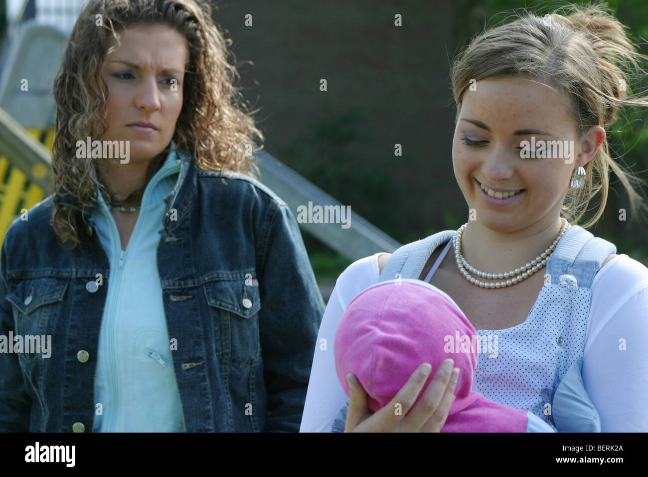 Woman looking jealous at friends baby - Stock Image