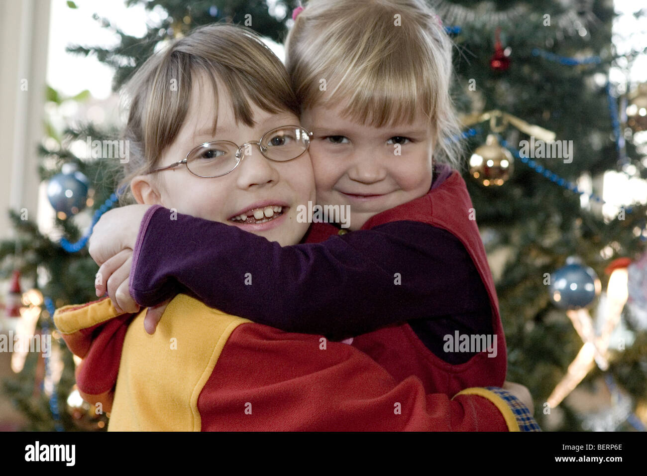 Siblings cuddling in front of Christmas tree, happy young sisters embrace each other at home xmas. - Stock Image