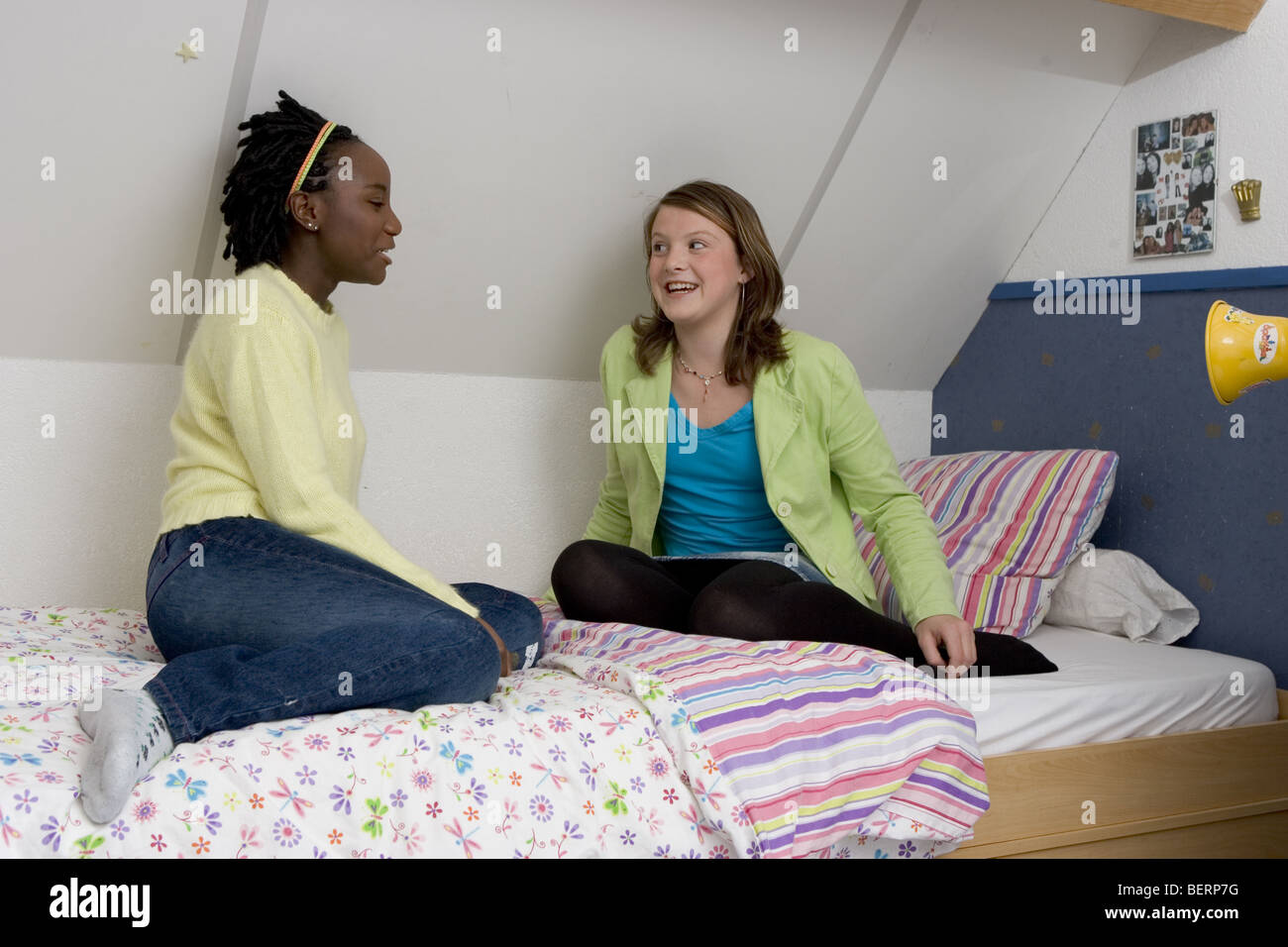 Black african and white caucasian teenage girls having a conversation on bed sit - Stock Image