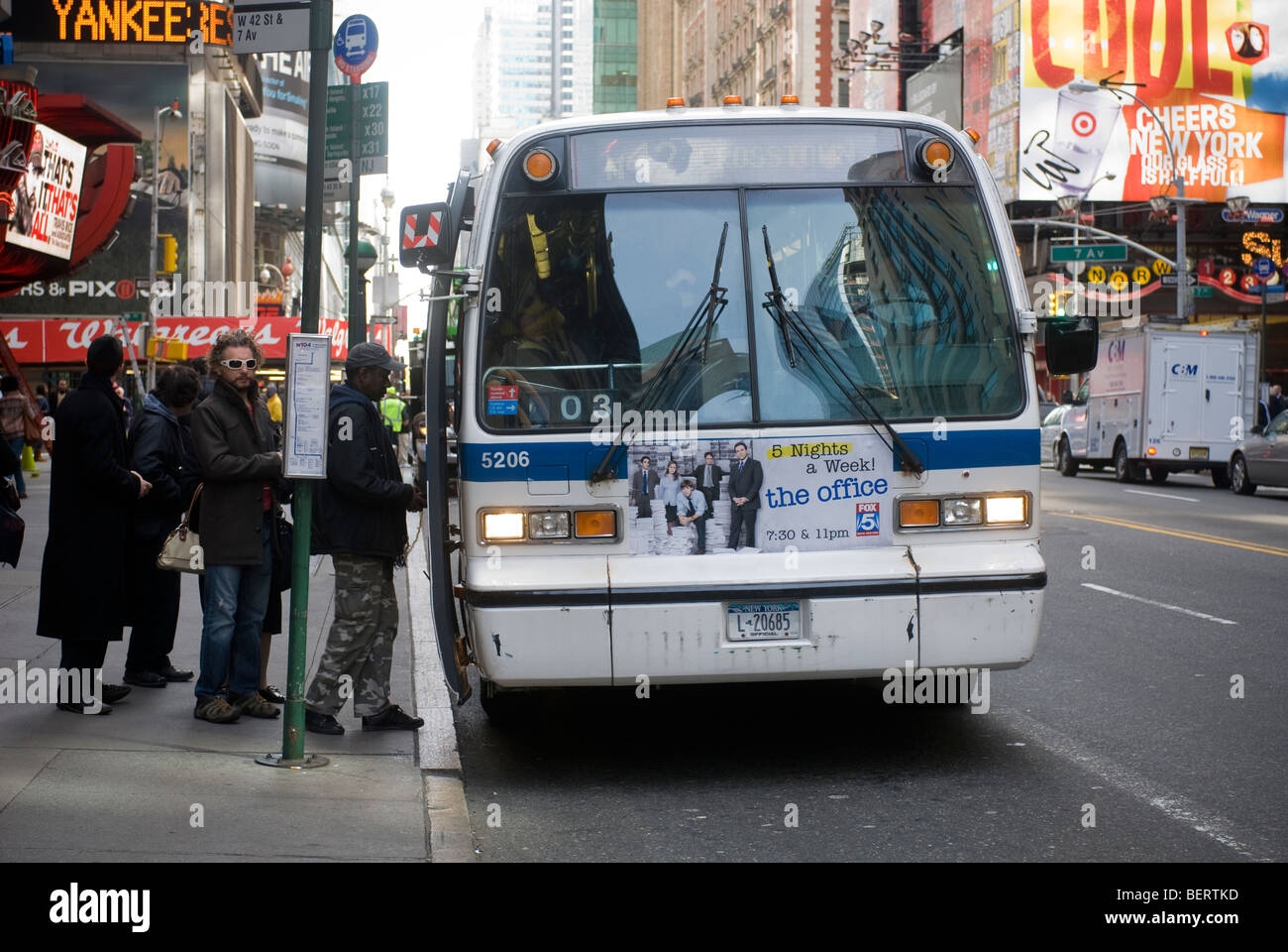 Riders board and exit a bus in Midtown Manhattan in New York - Stock Image