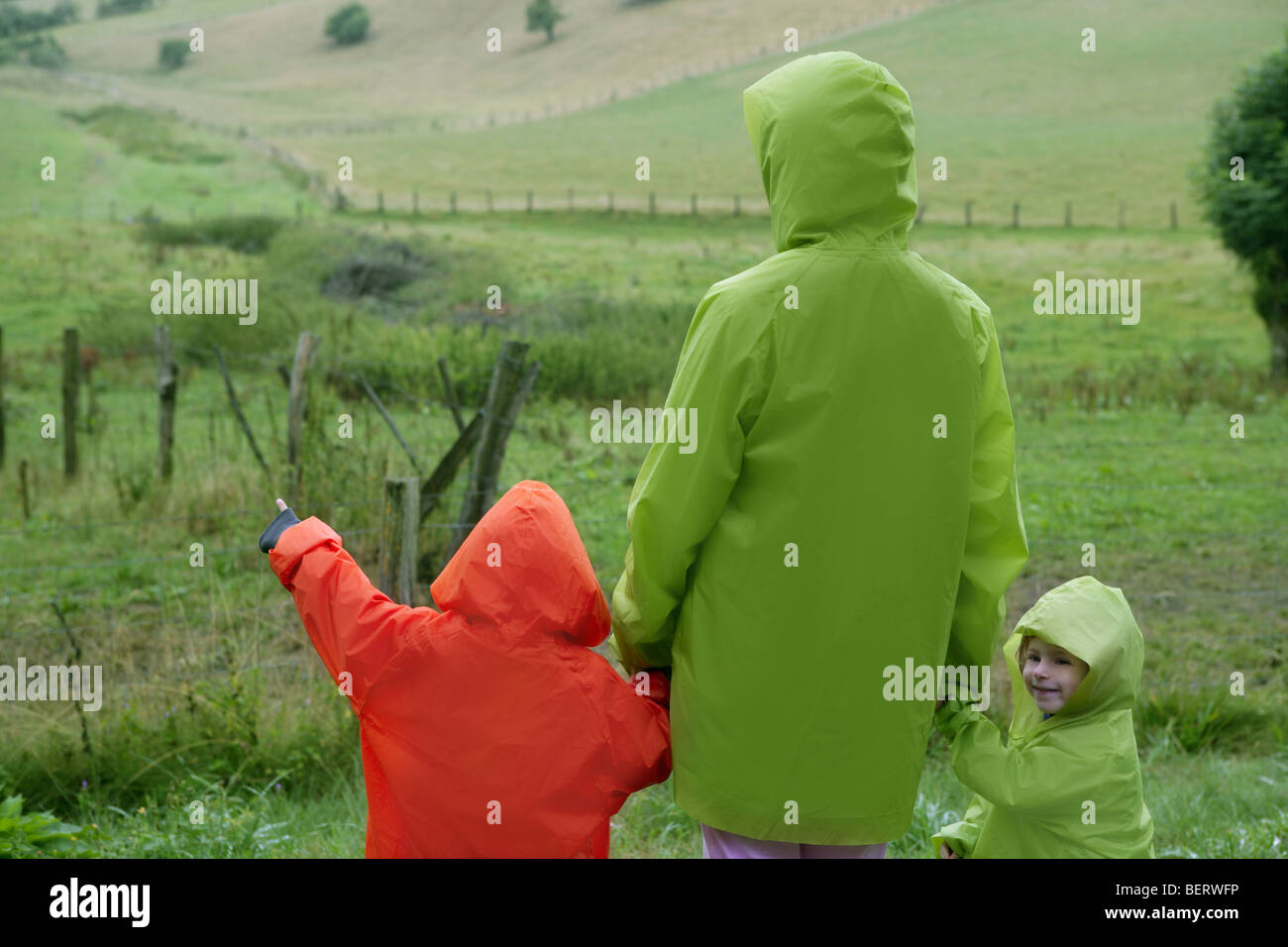 Green meadow with plastic waterproof coat colorful family in front - Stock Image