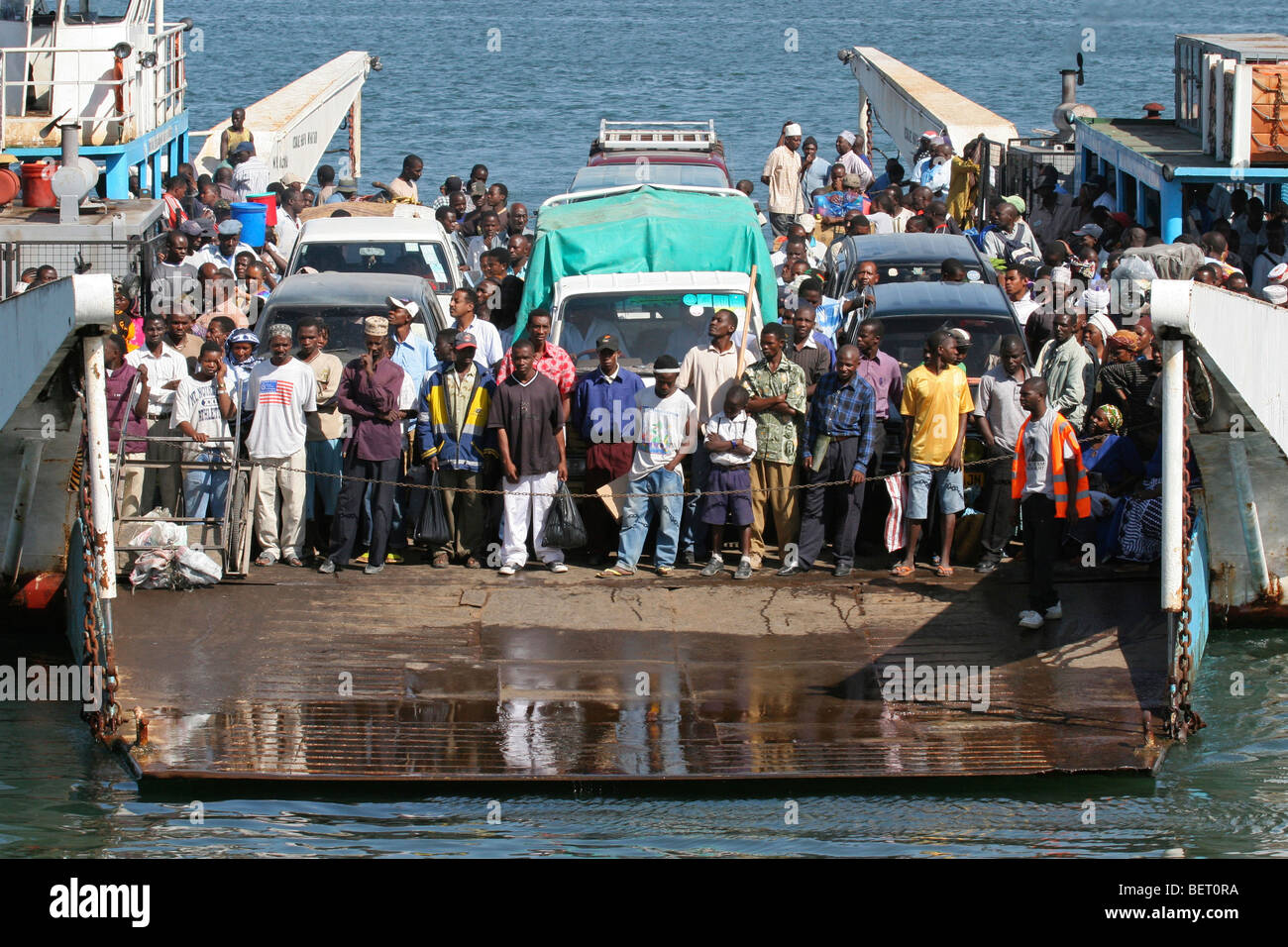 Black passengers and vehicles on ferry boat at Dar es Salaam, Tanzania, Africa - Stock Image