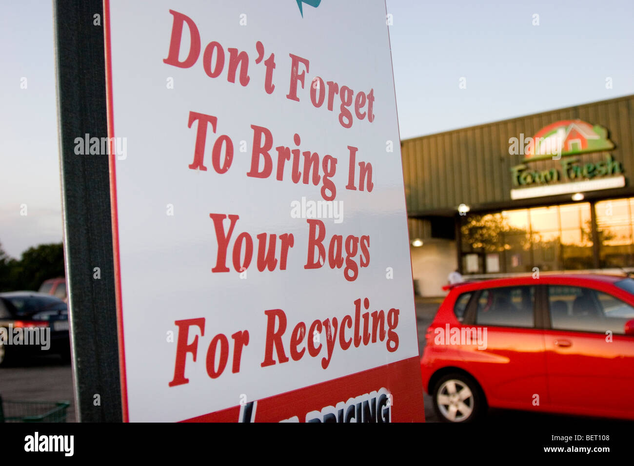 Grocery store parking lot sign reminding shoppers to bring bags for recycling - Stock Image