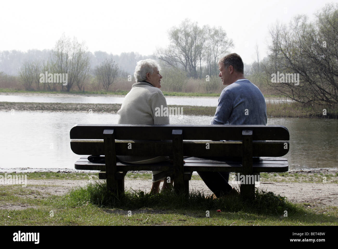 Senior woman and adult son talking seriously about the past on a bench in nature at lake , mother give sound advice Stock Photo