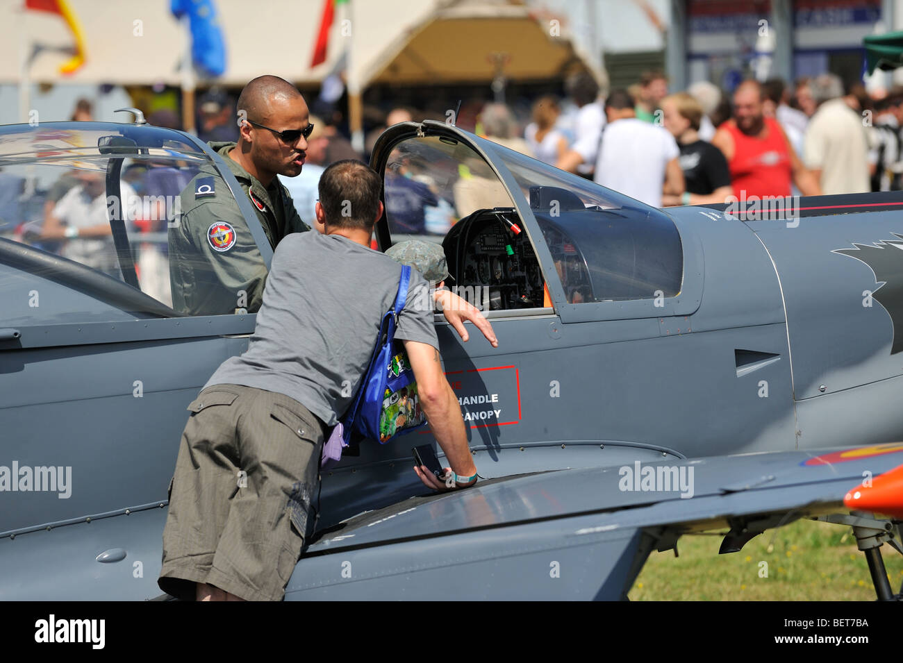 Pilot showing airplane cockpit to tourists at airshow in Koksijde, Belgium - Stock Image