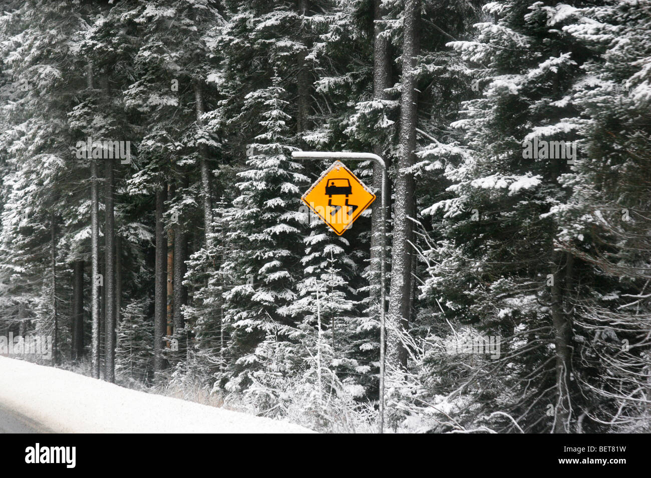 Road side sign shows slippery road ahead, Vancouver, British Columbia, Canada - Stock Image