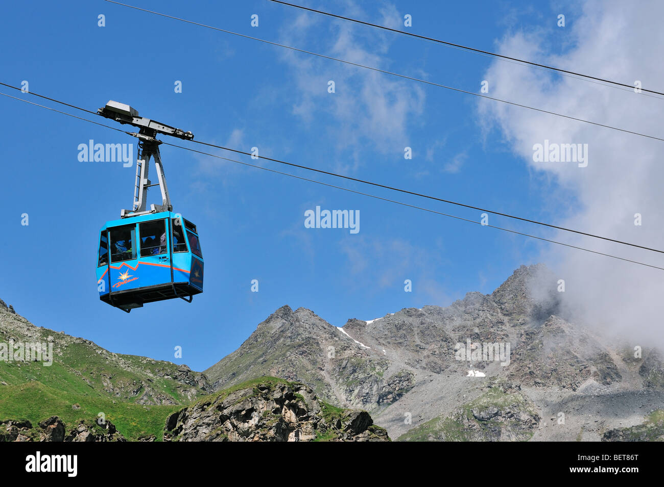Tourists in cable car / cableway / cable-lift on a cloudy day in the mountains, Swiss Alps, Switzerland - Stock Image