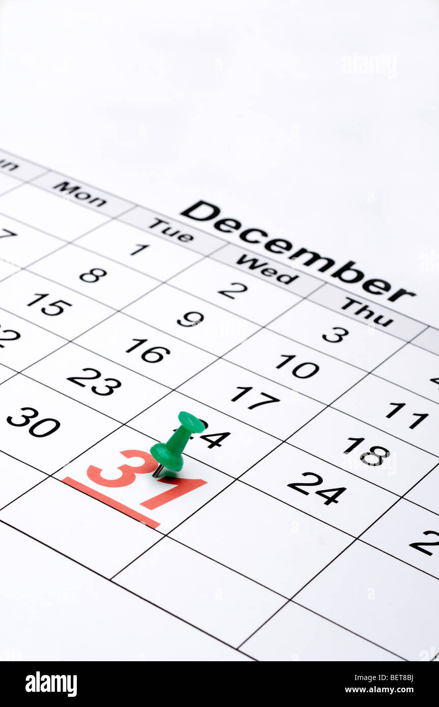 Vertical image of a calendar with New Year's day marked with a green tack - Stock Image
