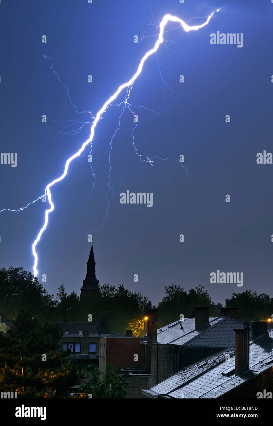 Lightning bolt over houses and church tower at night during thunderstorm Stock Photo