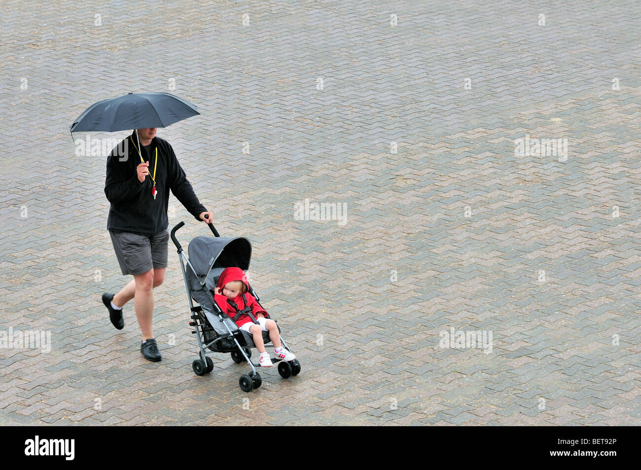 Dad with umbrella and baby in pram walking over promenade along the coast at seaside resort on rainy day during - Stock Image