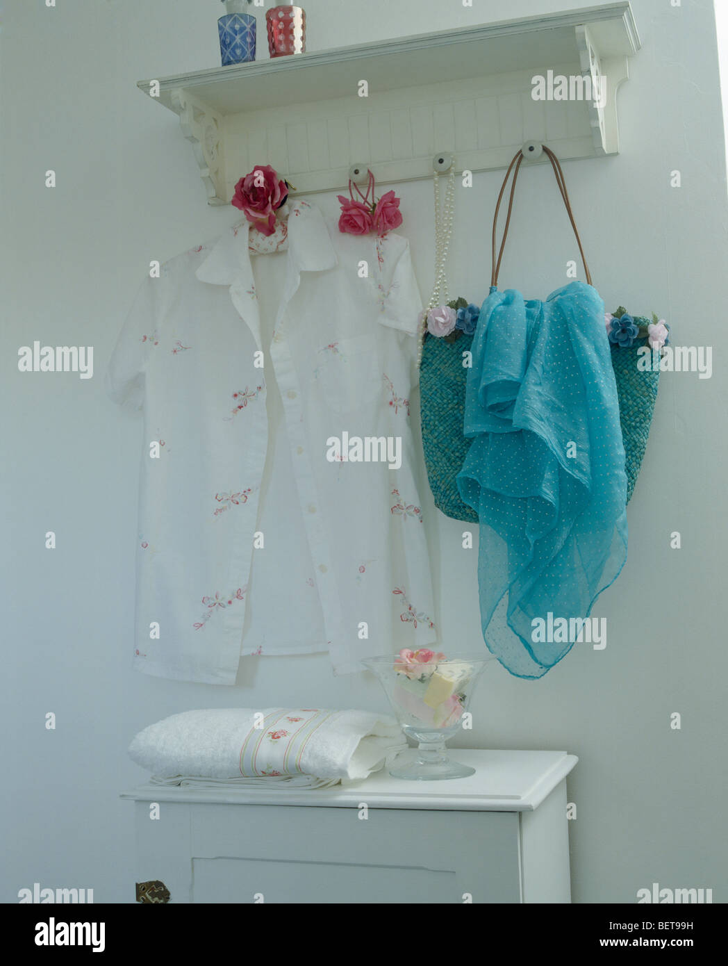 Close-up of white blouse and blue chiffon scarf on white pegboard - Stock Image