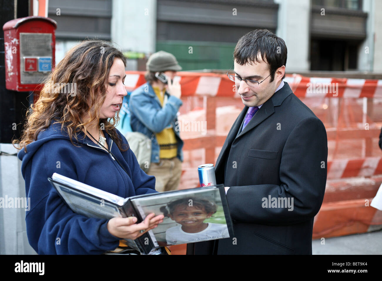 earnest young woman with curly hair pitches a charitable cause to a patient young businessman on Broadway in Lower - Stock Image