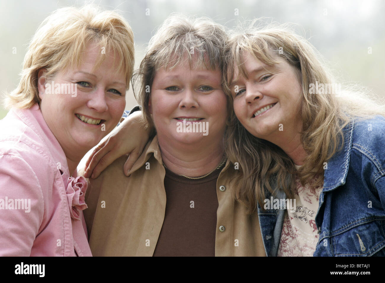 Happy portrait tree mature sisters over 40 happy look at camera. - Stock Image