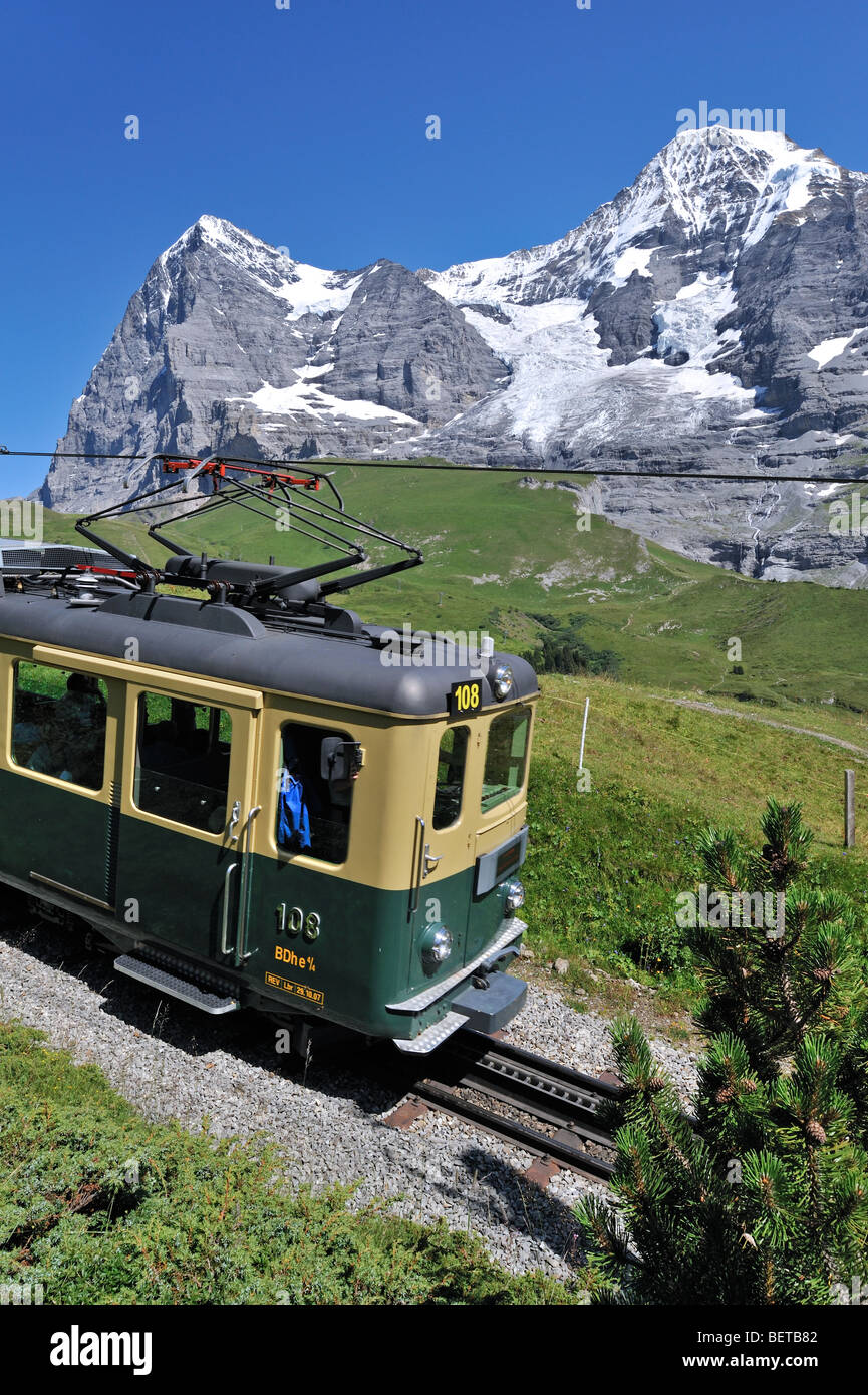 The Eiger and Monch mountains and Swiss train coming from the Kleine Scheidegg in the Bernese Alps, Swiss Alps, - Stock Image