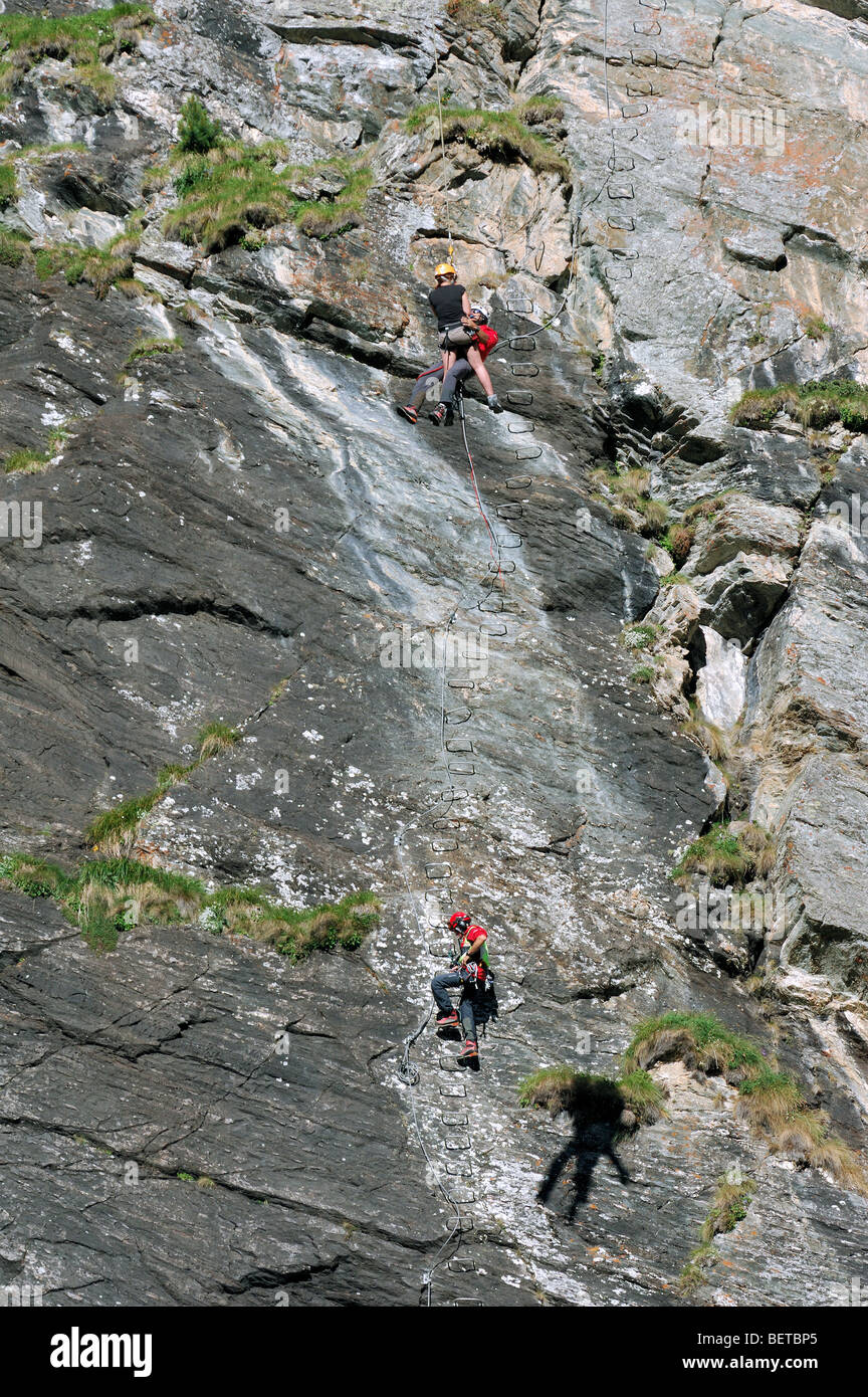 Swiss rescue helicopter winching rescuer and climber / victim from via ferrata / rock face in the Alps, Switzerland - Stock Image