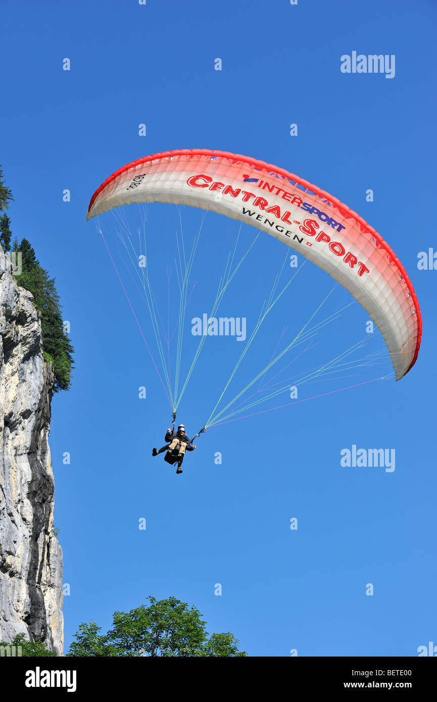 Tandem paraglider with pilot and passenger flying along rock face in the Swiss Alps, Switzerland - Stock Image