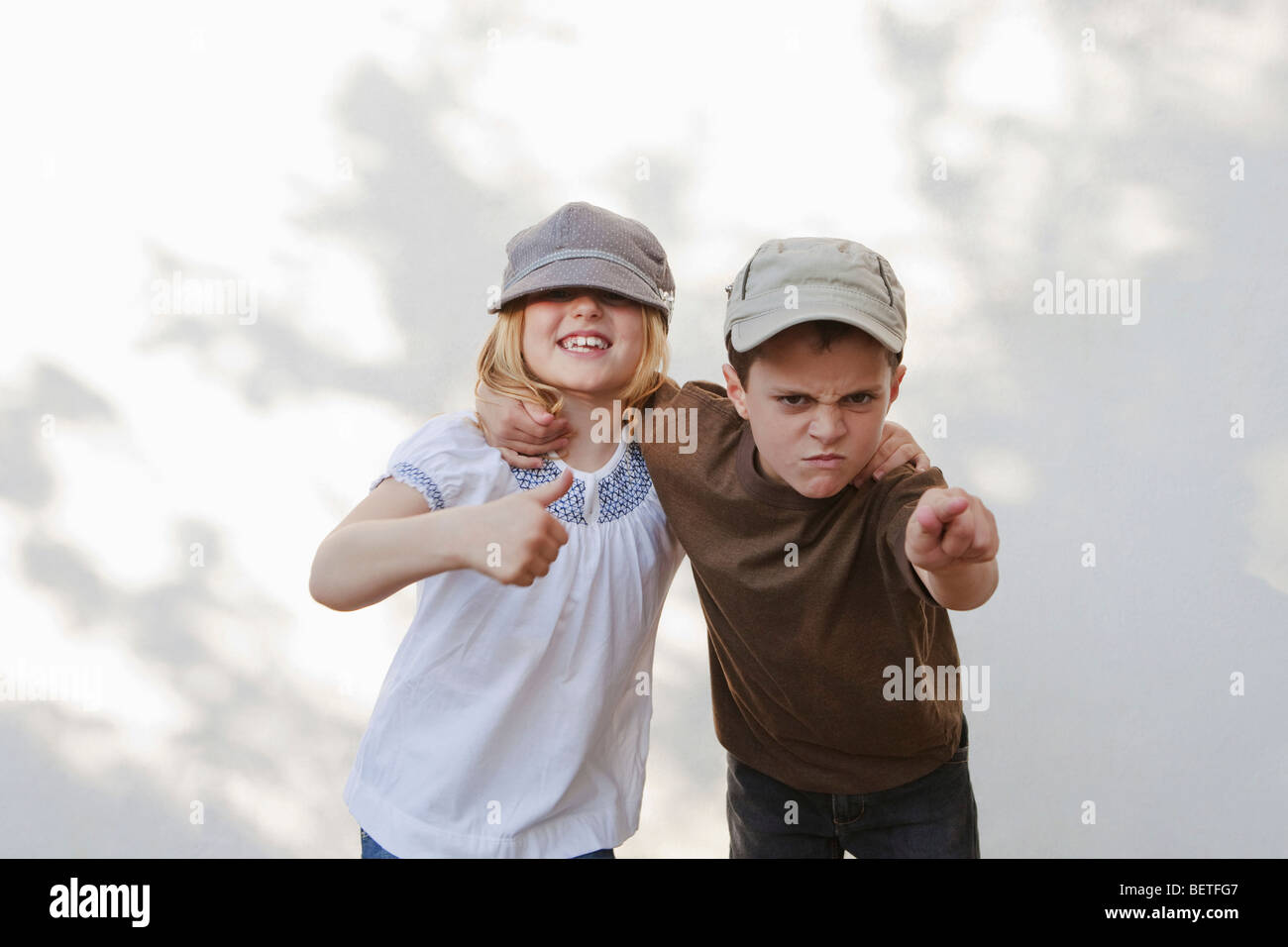 Boy pointing with girl giving thumbs up - Stock Image