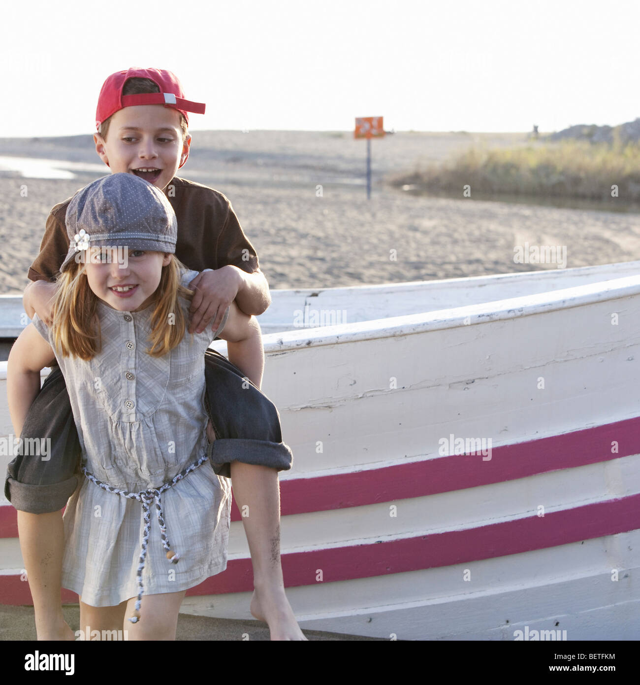 Girl Giving Piggyback To Boy By Boat Stock Photo: 26354712