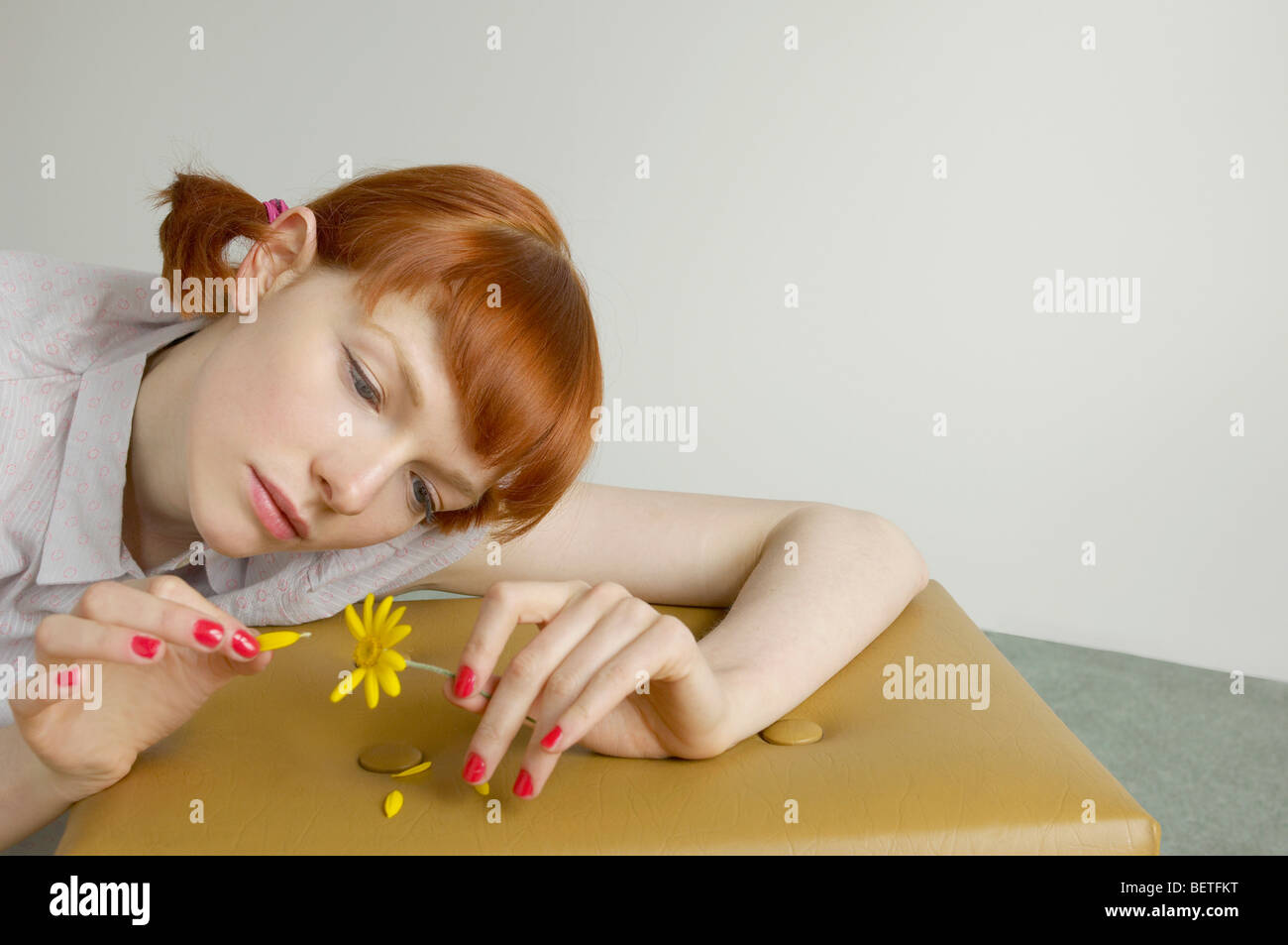 woman pulling petals from daisy Stock Photo