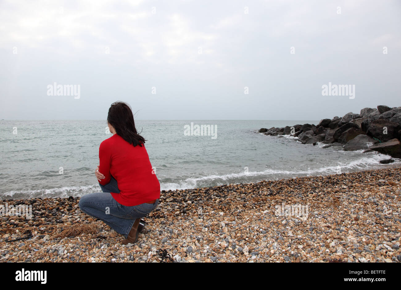 Back view of slim dark haired woman looking away into the distance. - Stock Image