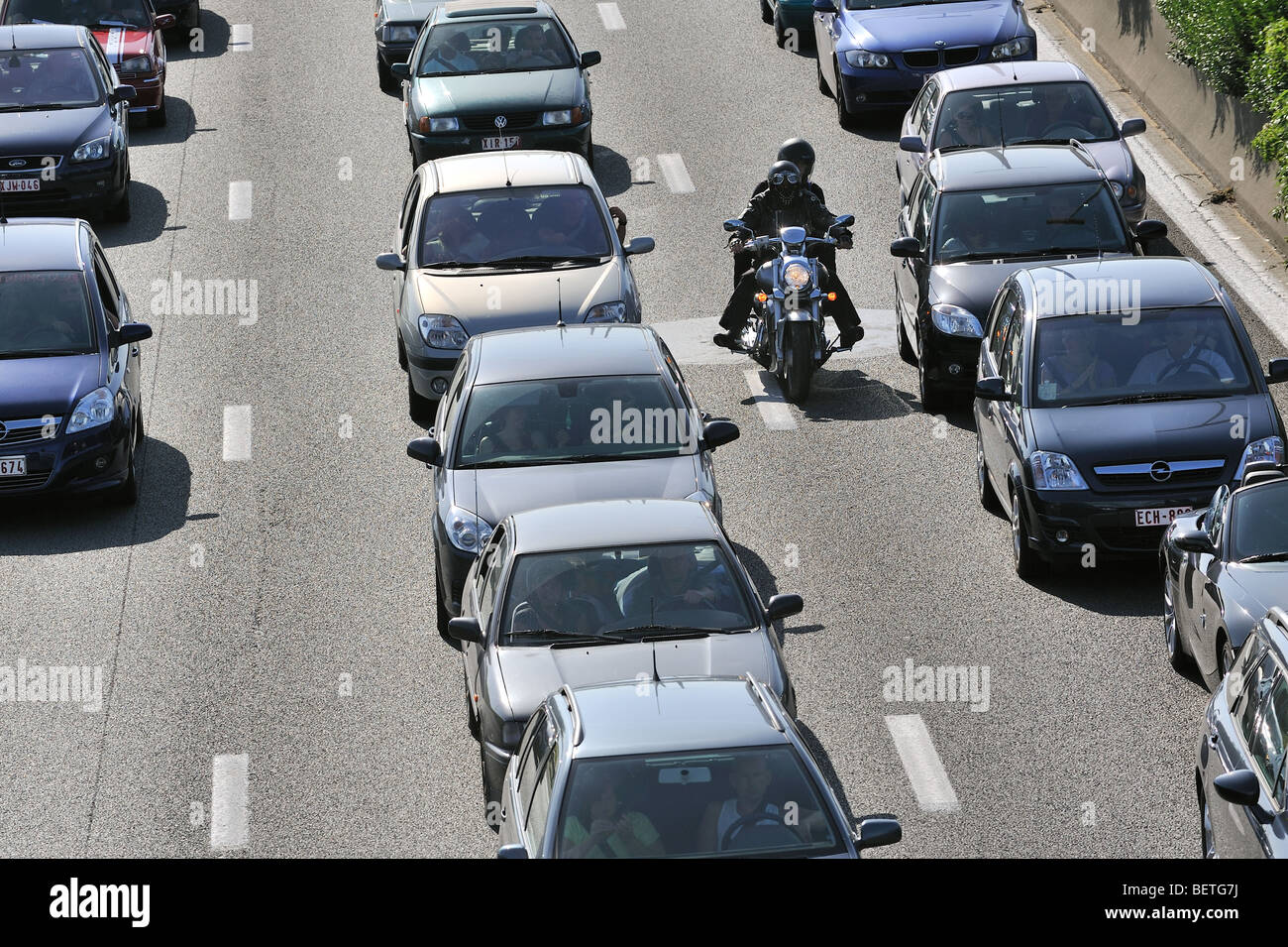 Motorcyclist riding between cars in traffic jam on motorway during the summer holidays, Belgium Stock Photo