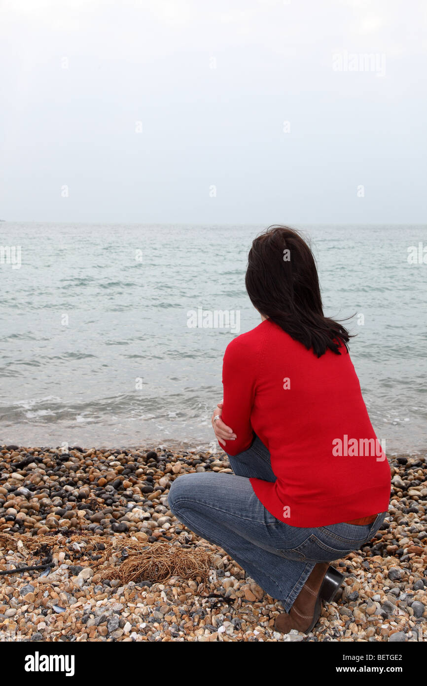 Back view of slim dark haired woman looking away into the distance - Stock Image