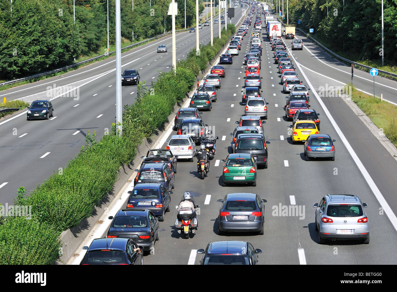 Cars and motorcyclists queueing in highway lanes at approach slip ...