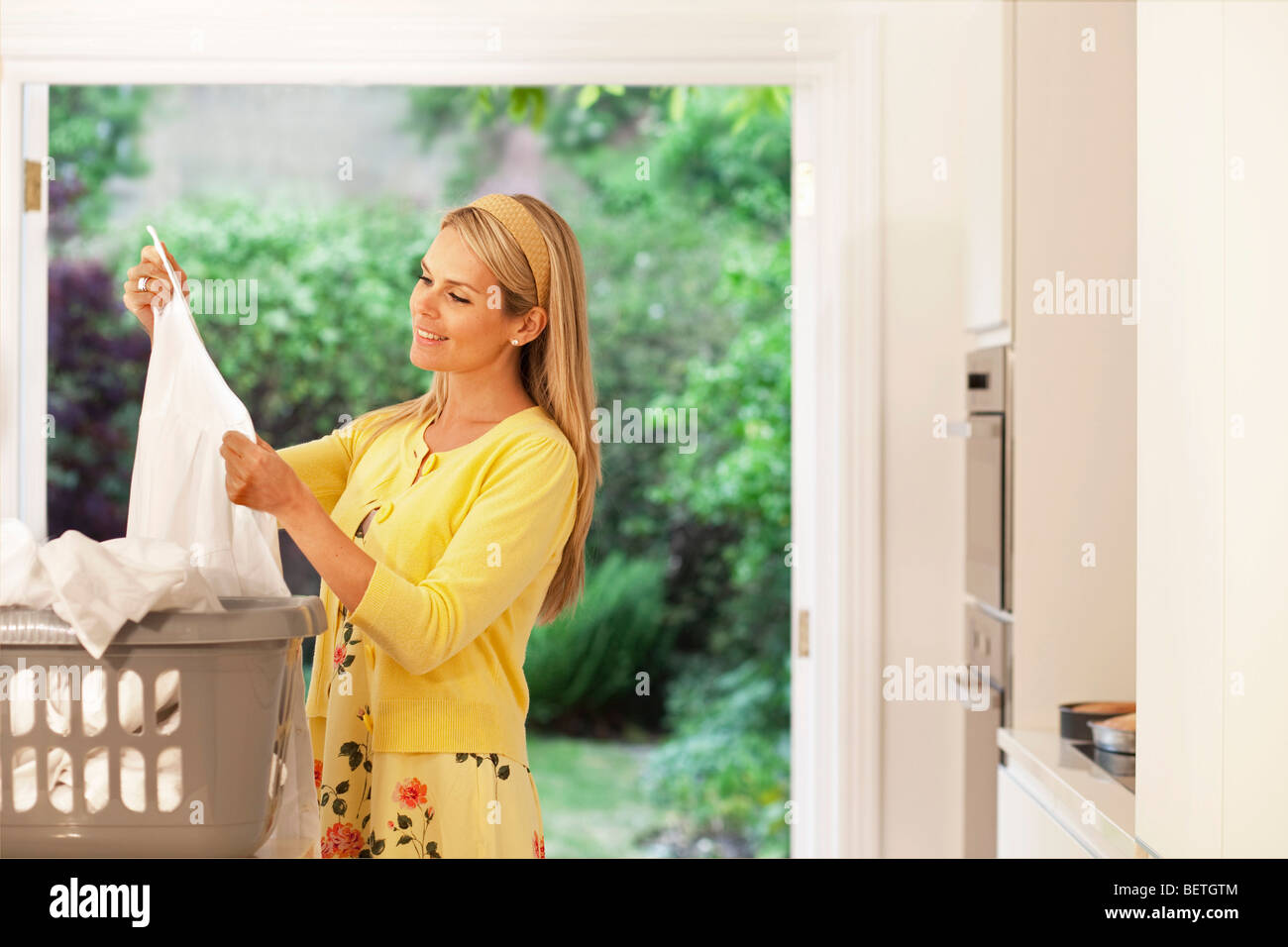 Beautiful young housewife doing laundry - Stock Image