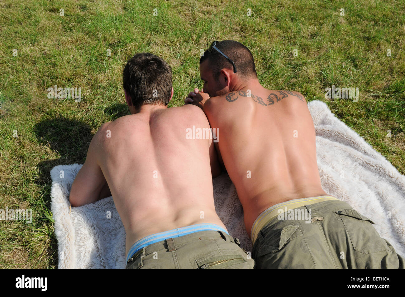 Young White Gay Couple Sunbathing In A Park In The Sunshine