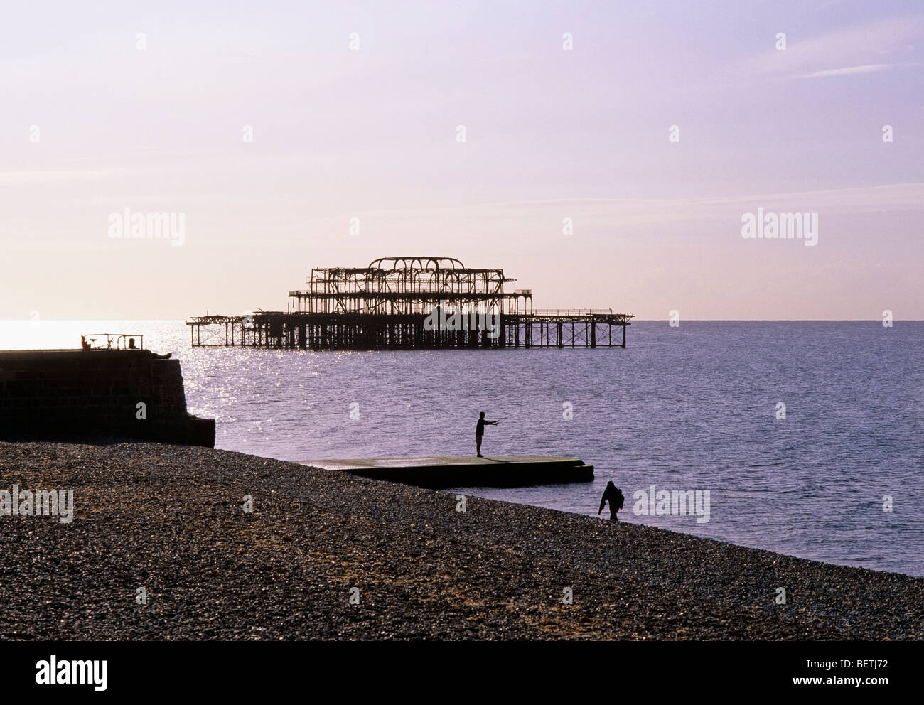 Autumn morning across the shingle beach at Brighton with the burnt out West Pier metal shell - Stock Image