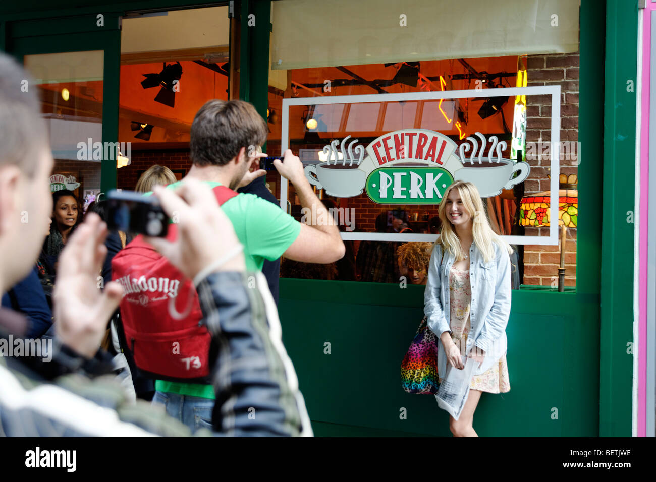Fans of TV series 'Friends' having their picture taken outside mock up of Central Perk cafe. London. Britain. - Stock Image