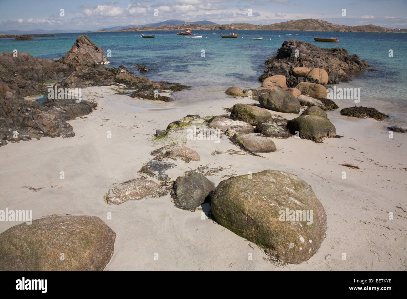 Iona white sands, beach and rocks looking out to the sound of mull and small boats. Isle of mull in the distance - Stock Image