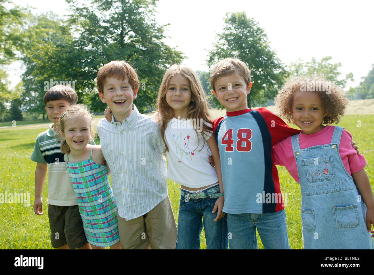 group of six young children in the park standing next to each other