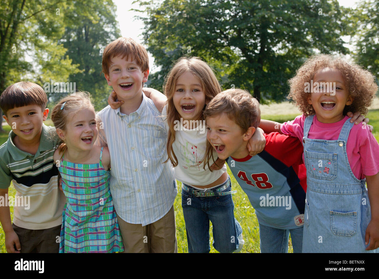 group of six children in the park laughing with their arms around each other - Stock Image