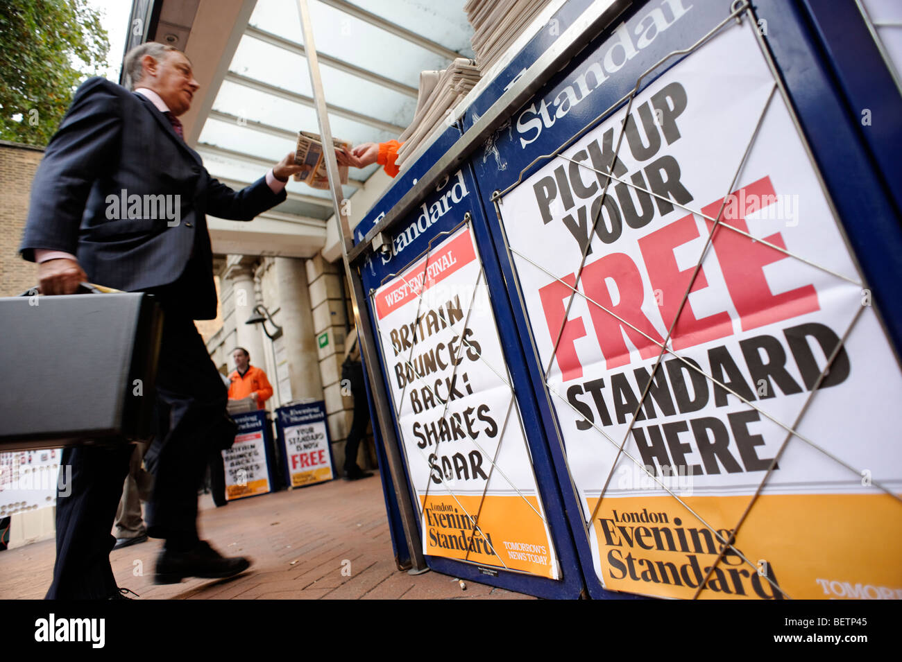 Person taking a free copy of the London Evening Standard newspaper. Central London. Britain. UK - Stock Image