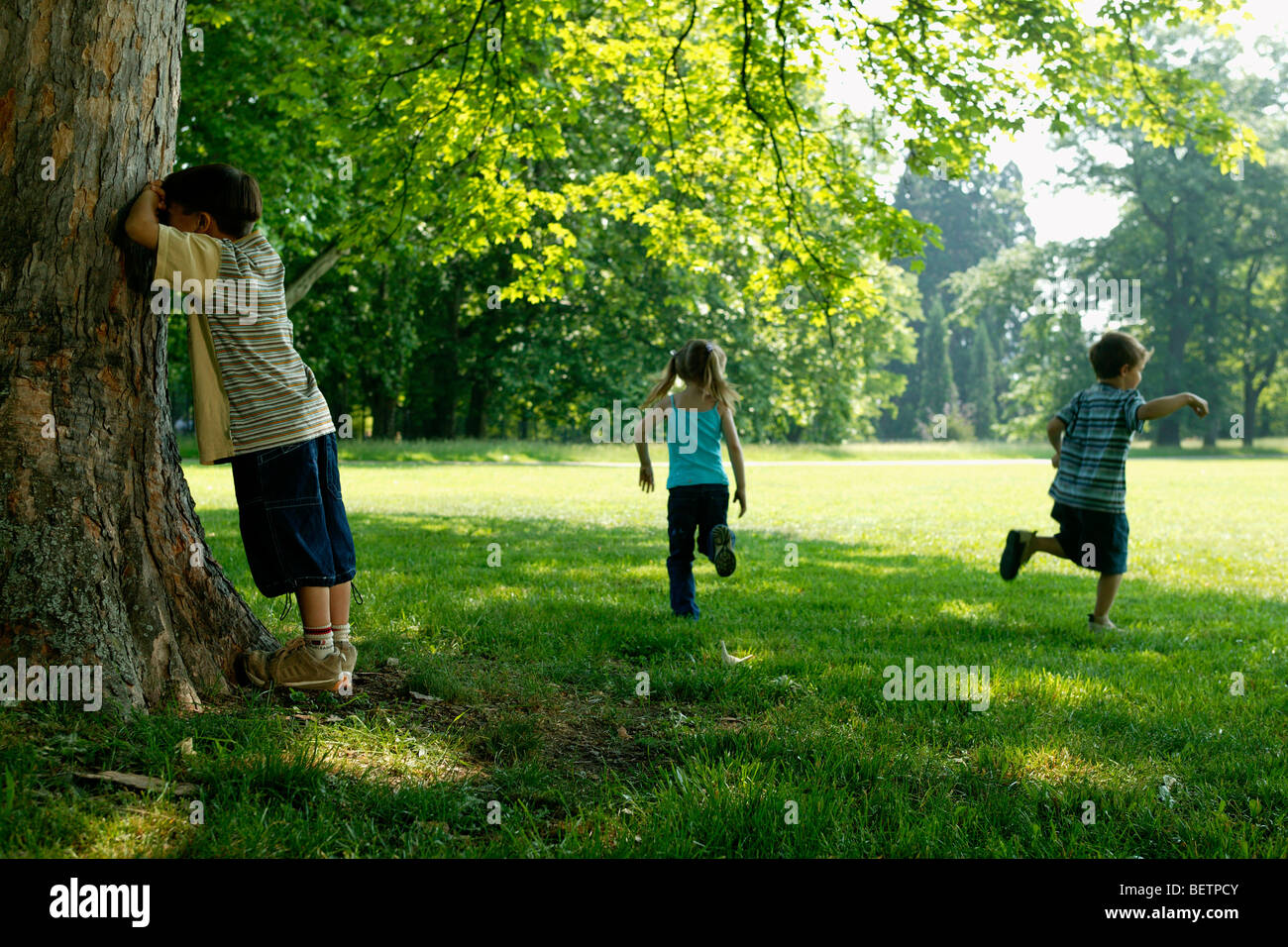 three children playing hide and seek in the park stock