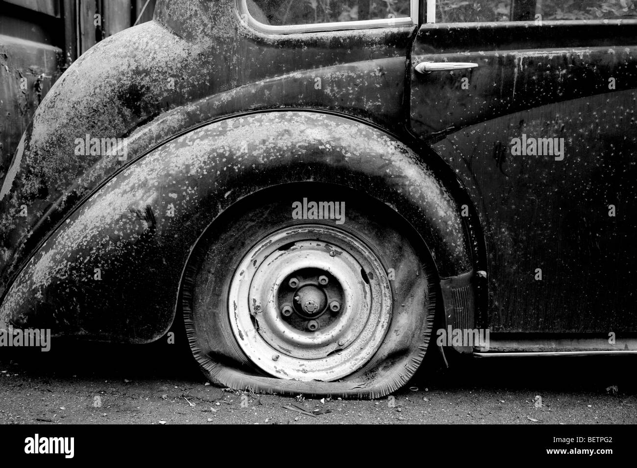 Old (1950s?) rusting car with flat tyre - Stock Image