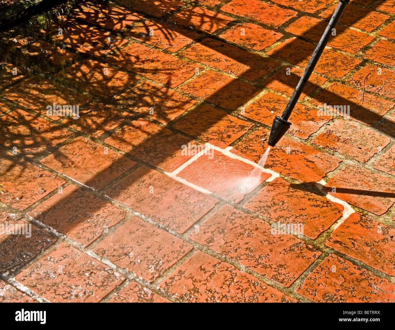 Cleaning a brick patio with a pressure washer Stock Photo
