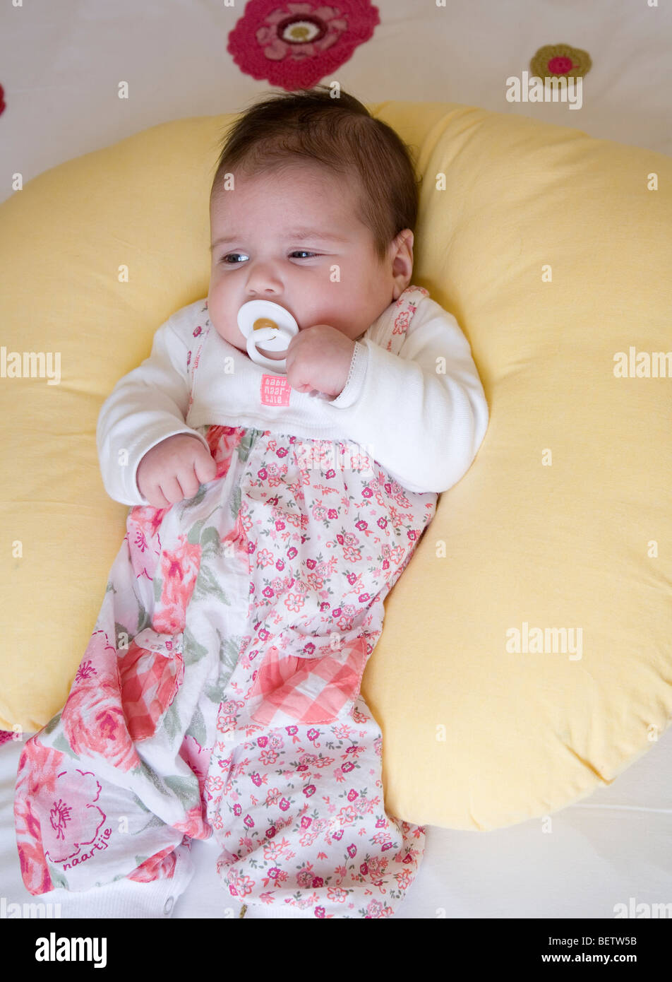 Baby sits up against a yellow support ring Stock Photo: 26362151 - Alamy
