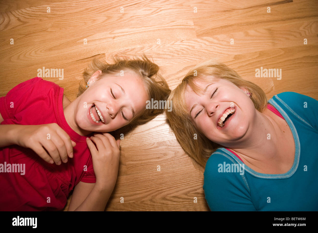 Two sisters laughing hysterically on a wood floor, ages 11 and 14 - Stock Image