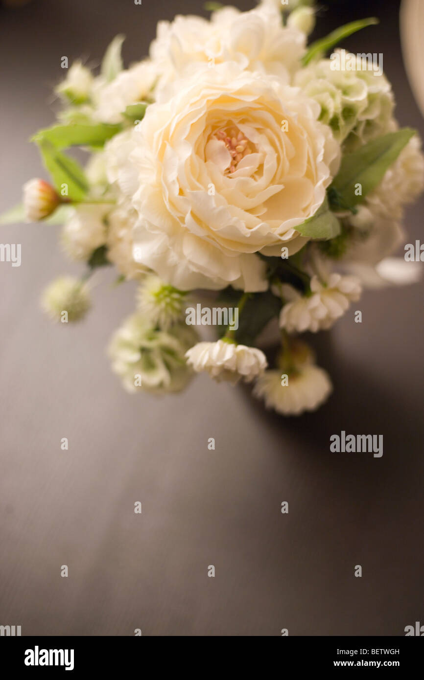 simple arrangement of peonies and white roses for a wedding, reception table bouquet - Stock Image