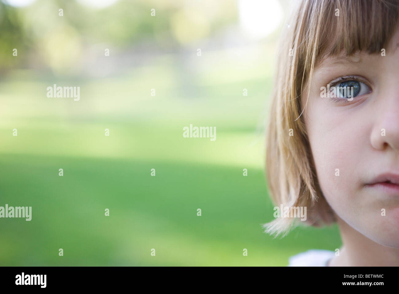 seven year old girl looking at camera with serious expression, green background, outdoors, closeup of face Stock Photo
