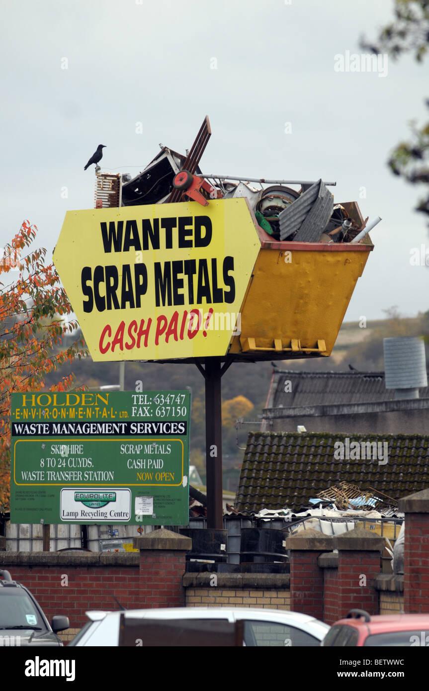 A skip full of scrap metal held aloft to advertise a scrap metal yard. - Stock Image