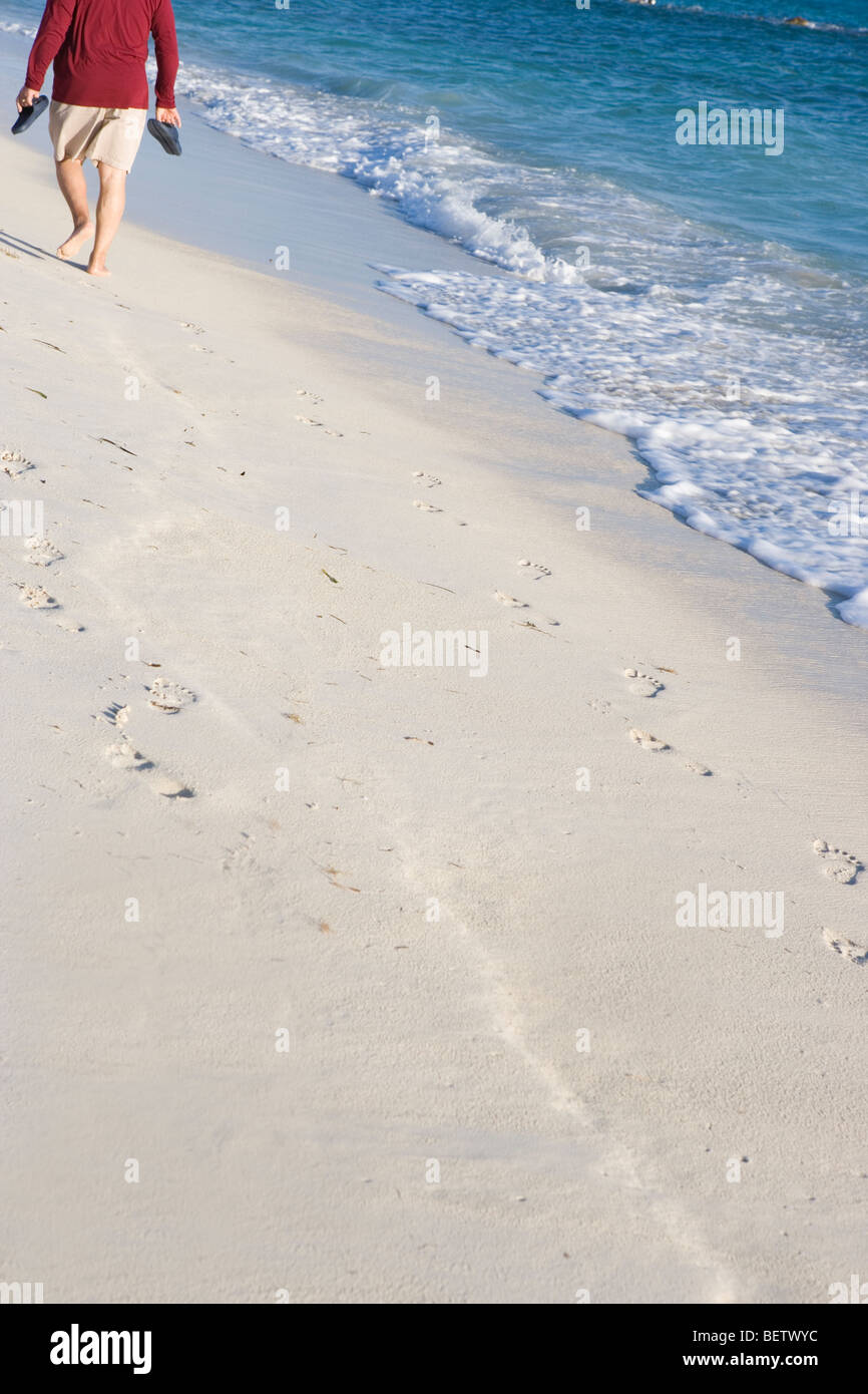 male senior citizen walking along a sandy beach carrying his sandals, early morning walk - Stock Image