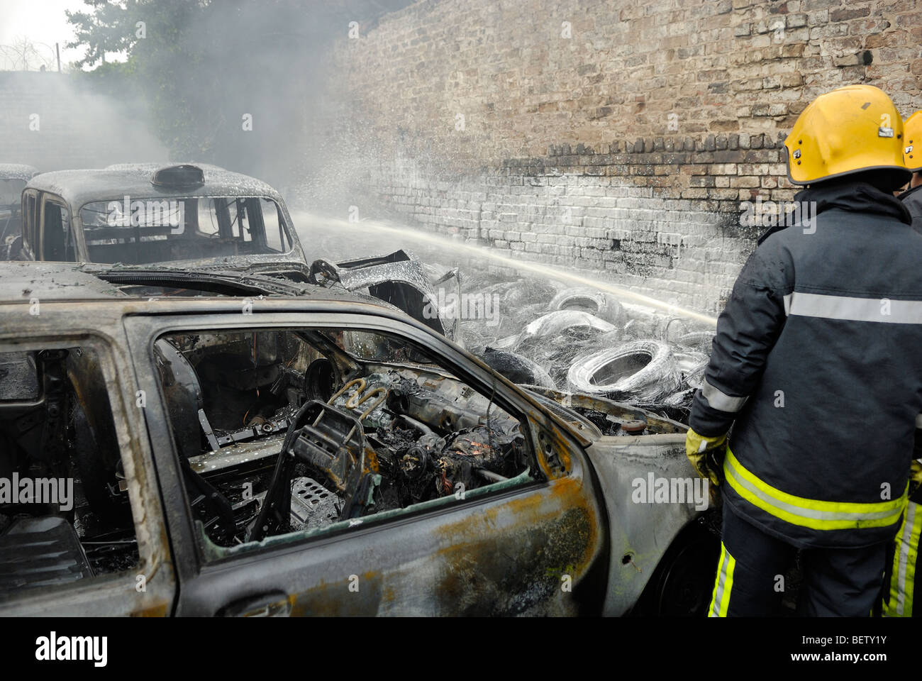 Car scrapyard on fire full of hackney cab taxis - Stock Image