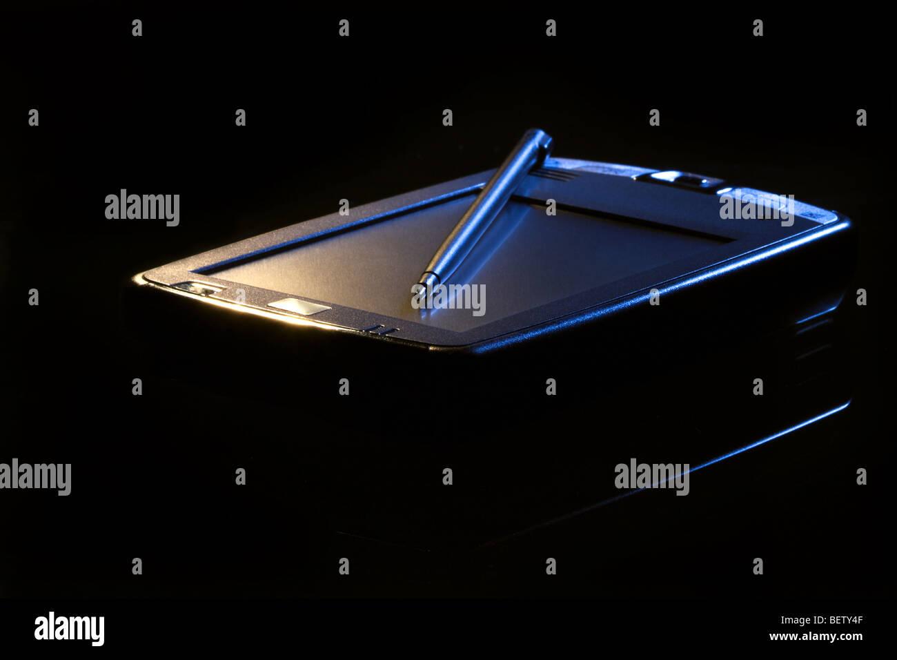 PDA in light beam. Black background. Close-up scene. - Stock Image