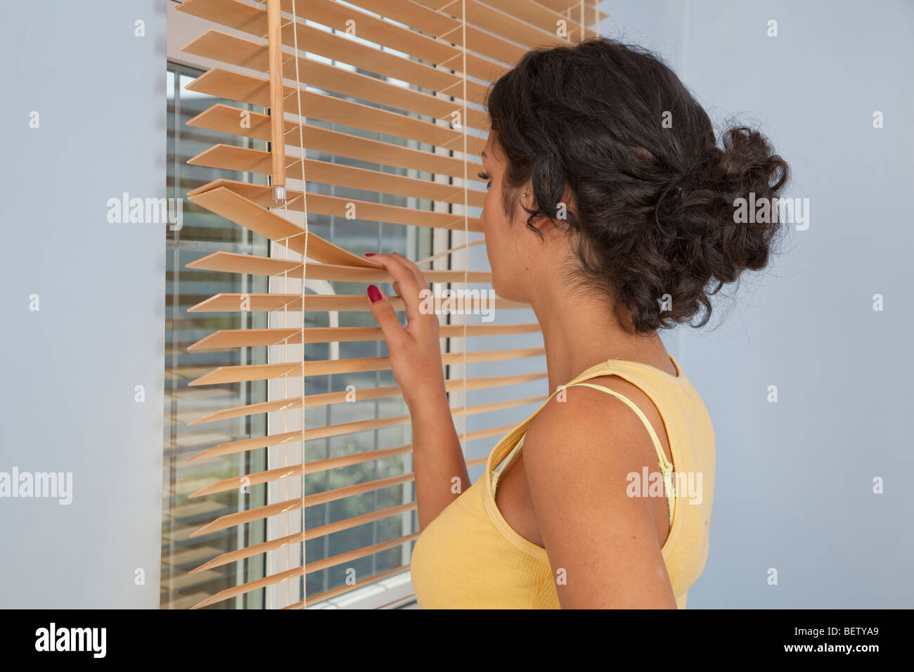Young woman looking out of a window through blinds Stock Photo